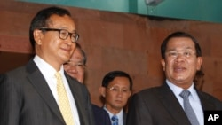 FILE PHOTO - Cambodian Prime Minister Hun Sen, right, talks with the main Opposition Party leader Sam Rainsy, left, of Cambodia National Rescue Party, after their meeting in Senate headquarters in Phnom Penh, Cambodia, Tuesday, July 22, 2012. (AP Photo/Heng Sinith)