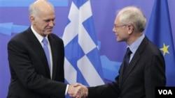 PM Yunani George Papandreou berjabat tangan dengan Presiden Dewan Eropa, Herman van Rompuy di Brussels, Belgia.
