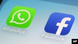 FILE - WhatsApp and Facebook app icons on a smartphone.