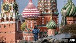 Una persona de seguridad está de guardia en el parque Zaryadye, con la torre Spasskaya del Kremlin y la Catedral de San Basilio vistas al fondo, en el centro de Moscú el 24 de marzo de 2020.