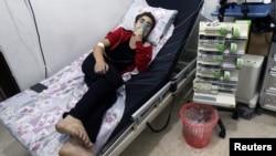 Seorang warga bernapas melalui masker oksigen di RS al-Quds akibat serangan gas klorin di Aleppo, Suriah Kamis (11/8).