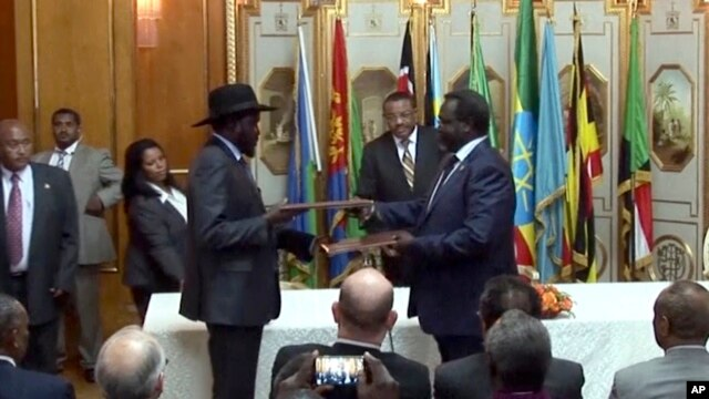 FILE - In this image made from video, South Sudan's President Salva Kiir, center left, and rebel leader Riek Machar, center right, exchange the signed documents in Addis Ababa, Ethiopia, May 9, 2014.