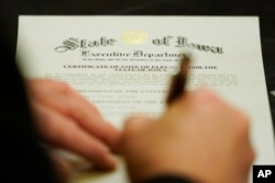 A member of Iowa's Electoral College signs the Certificate of Vote of Electors for the State of Iowa, Monday, Dec. 14, 2020, at the Statehouse in Des Moines, Iowa. (AP Photo/Charlie Neibergall)