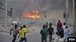 Asap mengepul dari kantor polisi pusat di Kano, Nigeria, sementara warga yang panik berlarian menyelamatkan diri (20/1).