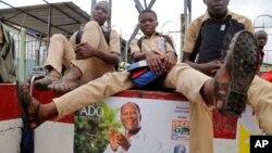 Des enfants assis sur un mur sur lequel est affiché un poster du président sortant de la Côte d'Ivoire, Alassane Ouattara, le 21 octobre 2015. (AP Photo/Schalk van Zuydam)