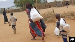 A newly arrived Somali family carry their supply of aid outside Dadaab, Eastern Kenya, Aug. 5, 2011. (AP)