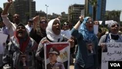 Para pendukung Hosni Mubarak, yang menentang pengadilan atas mantan presiden yang kini sakit itu, melakukan protes di Kairo dengan membawa poster Mubarak, Jumat (24/6).