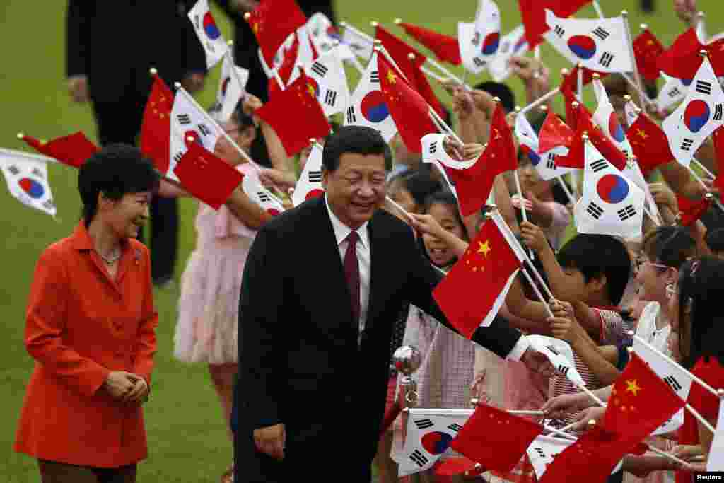 Chinese President Xi Jinping and South Korean President Park Geun-hye greet children waving the two countries' national flags during a welcoming ceremony at the presidential Blue House in Seoul, July 3, 2014.