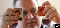 In this Thursday, Feb. 13, 2020, photo, James Kretschmer holds photographs of himself at age 11 and 12 during an interview in Houston. Kretschmer says he was sexually abused by a Scout leader over several months in the mid-1970s in the Spokane, Washingto