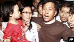 ທ່ານ Jim Mee (ຂວາ) ແລະນາງ Nilar Thein (ກາງ) ຊຶ່ງເປັນພວກນັກເຄື່ອນໄຫວຂອງກຸ່ມ ນັກສຶກສາ 88 ໄດ້ຮັບການຕ້ອນຮັບຈາກລູກສາວຂອງພວກຕົນ (ຊ້າຍ) ທີ່ສະໜາມບິນນະຄອນ ຢ້າງກຸ້ງ ພາຍຫລັງທີ່ ໄດ້ຖືກປ່ອຍຕົວອອກຈາກຄຸກໃນວັນສຸກ ທີ 13 ມັງກອນ, 2012, in Yangon (AP Photo/Khin Maung Win)