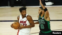 Sep 15, 2020; Lake Buena Vista, Florida, USA; Miami Heat forward Jimmy Butler (22) drives to the basket while Boston Celtics forward Jayson Tatum (0) defends during the first half in game one of the Eastern Conference Finals of the 2020 NBA Playoffs at ES
