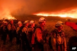 Firefighters from Cal Fire's Placerville station monitor the Sugar Fire, part of the Beckwourth Complex Fire, in Doyle, Calif., July 9, 2021.