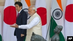 Indian Prime Minister Narendra Modi, right, shows the way to his Japanese counterpart Shinzo Abe as they arrive for their meeting, in New Delhi, India, Dec. 12, 2015.