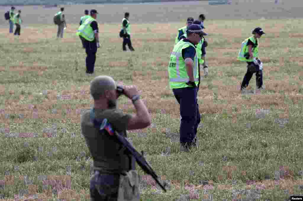 A pro-Russian separatist looks through binoculars as Dutch and Australian forensic experts continue recovery work at the site of the downed Malaysian airliner MH17 near the village of Rozsypne, in the Donetsk region, Aug. 4, 2014.
