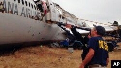 Investigadores examinan los restos del avión de Asiana Airlines accidentado en San Francisco.