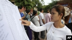 A woman finds her name on a list during a local commune election in Phnom Penh, file photo.