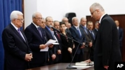Palestinian Prime Minister elect Rami Hamdallah, right, takes oath of office in front of President Mahmoud Abbas, June 6, 2013