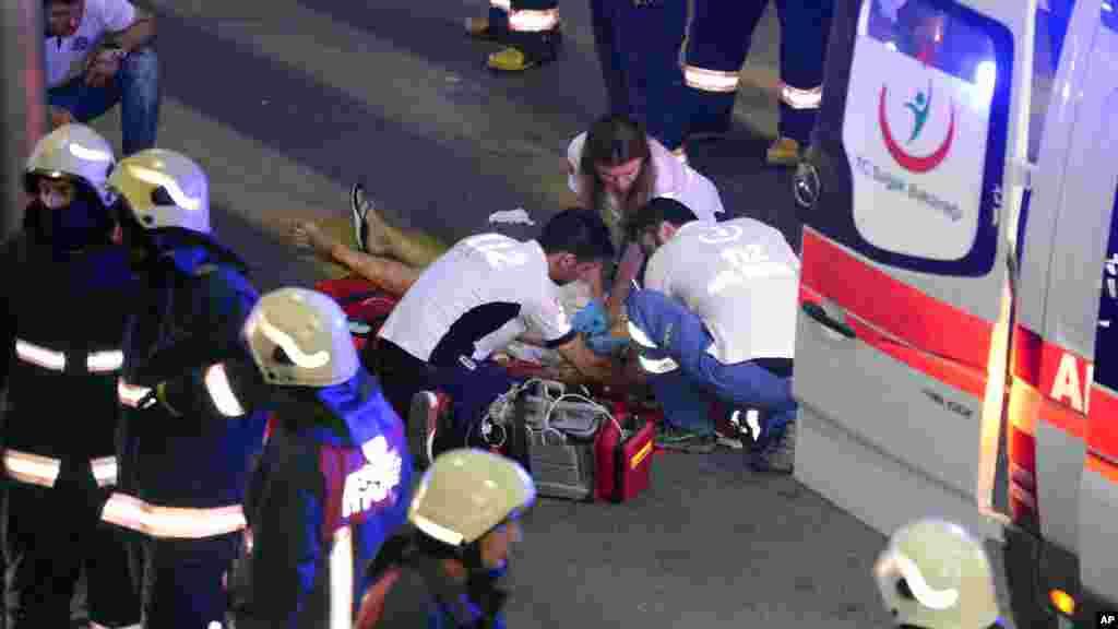Des secouristes aident une personne blessée à l'extérieur de l'aéroport.