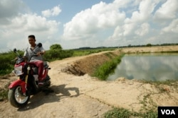 Chhum Phirom, 26, sits on a motorcycle near his fish pond in Peamror district, Prey Veng province, Cambodia, on July 22, 2020. (Aun Chhengpor/VOA Khmer)