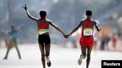 La Kényane Jemima Sumgong et la Baheïni Jepkirui Kirwa fêtent lors victoire lors du marathon, à Rio de Janeiro, Brésil, le 14 août 2016.