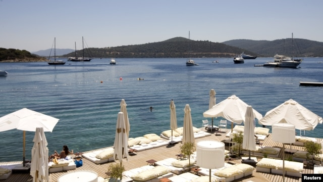 A woman sunbathes on a near-deserted deck as luxury boats are seen anchored off the beach front of a hotel in Golturkbuku, near the resort town of Bodrum on the southwest Aegean coast of Turkey, July 17, 2007.