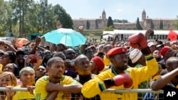 FILE - People attend 20-year Democracy Anniversary celebrations near to the government's Union Building, background, in Pretoria, South Africa, Sunday, April 27, 2014.