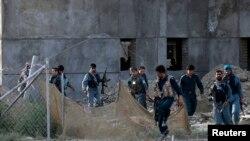 افغان پولیس د هغې ودانۍ شاته چې وسله وال په کې پټ شوي او پر هوايي ډګر ډزې کوي .