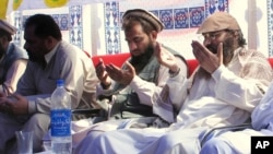 FILE - The alleged mastermind of the 2008 Mumbai attacks, Pakistani Zaki-ur-Rehman Lakhvi (C), is seen praying with others on June 28, 2008, in Muzaffarabad, capital of Pakistani Kashmir.