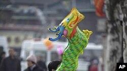 1月23号农历年初一,一名男子抱着龙形气球坐在上海龙华庙门口