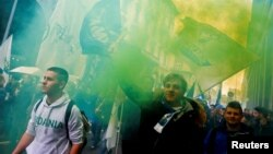 Italian League (Lega) supporters hold flares as they arrive at political rally led by leader Matteo Salvini, in Milan, Italy, Feb. 24, 2018.