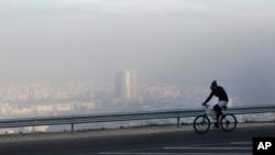 Un homme à vélo le long d'une route sur la montagne Vodno, avec en arrière-plan l'air pollué prévalant sur la capitale macédonienne Skopje, le 8 novembre 2015