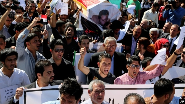 Mourners chant slogans during a symbolic funeral for the bureau chief of a local radio station in Baghdad, Iraq, March 23, 2014.