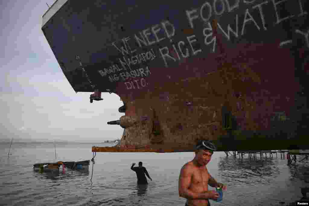 Divers take a part in an effort to recover a ship brought inland by Typhoon Haiyan in Tacloban, Philippines.