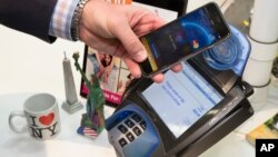 FILE - A customer makes a purchase with a MasterCard using Apple Pay on the iPhone 6 at Walgreens in Times Square in New York, Oct. 20, 2014.