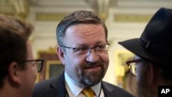 FILE - Sebastian Gorka, then a deputy assistant to President Donald Trump, talks with people in the Treaty Room in the Eisenhower Executive Office Building on the White House complex in Washington, May 2, 2017.