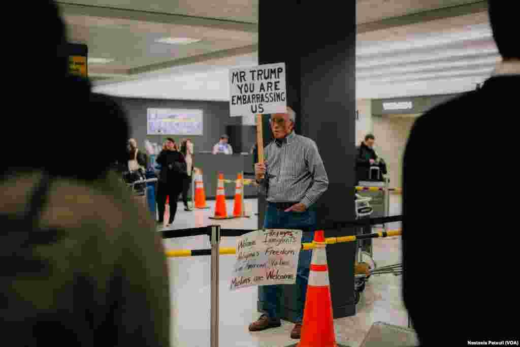 Des manifestants accueillent les touristes et les résidents à l'aéroport international de Washington DC, le 31 janvier 2017. (VOA/Nastasia Peteuil)