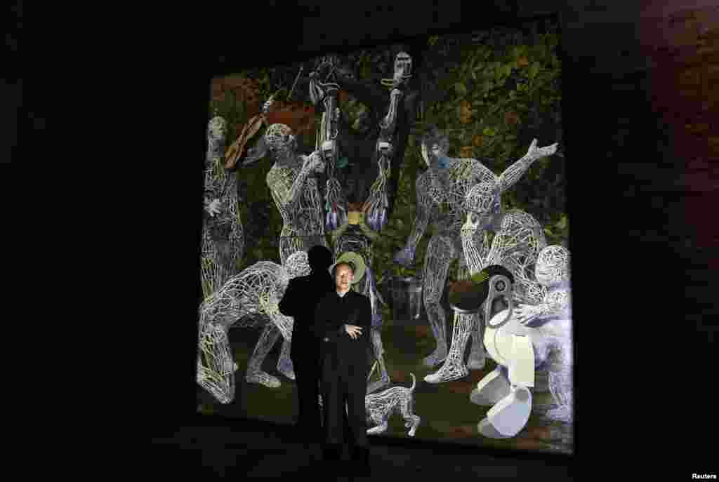 "Chinese artist Miao Xiaochun pose near his installation called ""Transfiguration"" at the China pavilion, May 28, 2013."