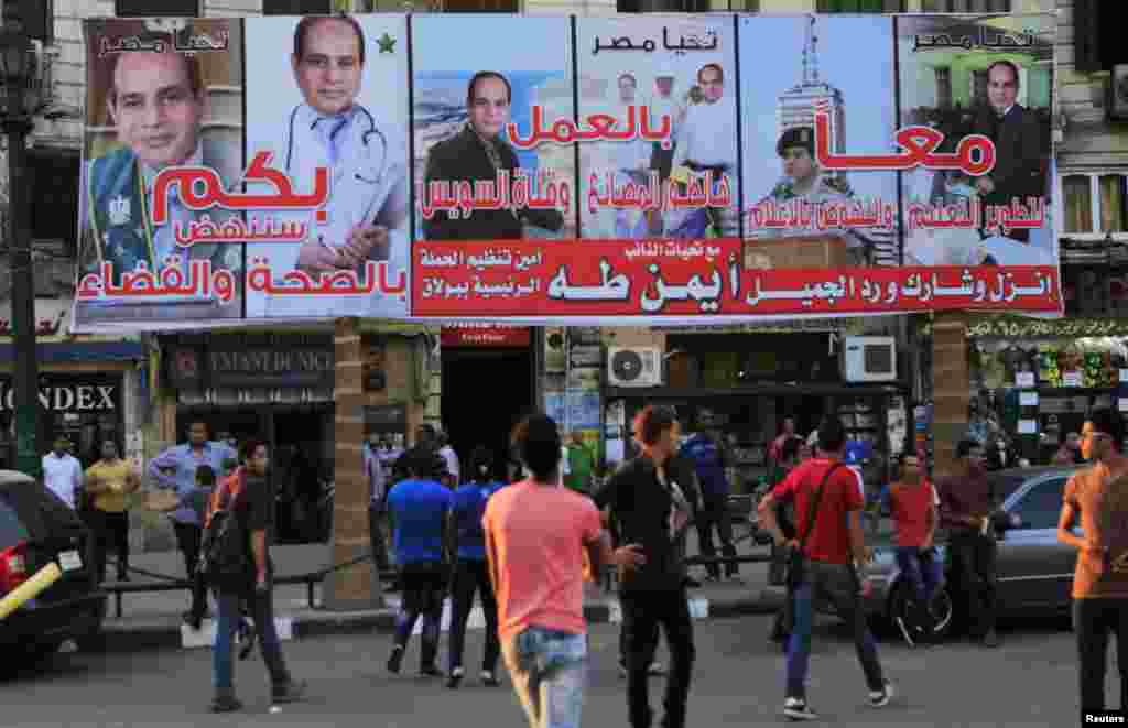 People walk under campaign posters of presidential candidate and former army chief Abdel Fattah al-Sissi a day ahead of presidential elections in Cairo, May 25, 2014.
