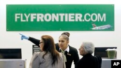 A Frontier Airlines employee wears gloves as she directs passengers where to go at Cleveland Hopkins International Airport . Ohio health officials aren't sure how many people came into contact with the Texas nurse who visited family in the state days before being diagnosed with Ebola.