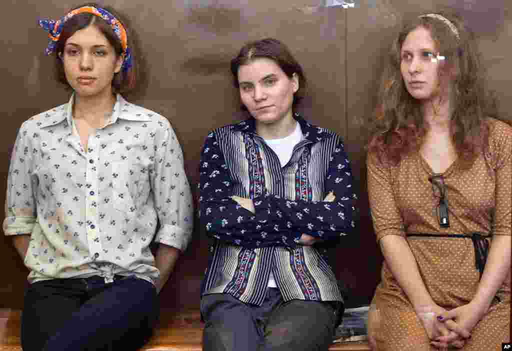 August 3: Pussy Riot members, from left, Nadezhda Tolokonnikova, Yekaterina Samutsevich and Maria Alekhina sit in a glass cage at a court room in Moscow, Russia.