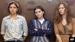 Pussy Riot members, from left, Nadezhda Tolokonnikova, Yekaterina Samutsevich and Maria Alekhina sit in a glass cage at a court room in Moscow, Russia, August 3, 2012.