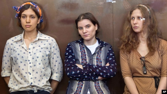 FILE - Pussy Riot members, from left, Nadezhda Tolokonnikova, Yekaterina Samutsevich and Maria Alekhina are seen in a glass cage in a court room during their trial in Moscow last year.