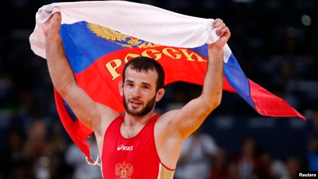 Russia's Dzhamal Otarsultanov celebrates after defeating Georgia's Vladimer Khinchegashvili on the final of the Men's 55Kg Freestyle wrestling during the London 2012 Olympic Games Aug. 10, 2012.