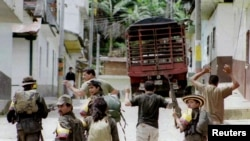 Anggota gerilyawan FARC menyandera tiga polisi yang ditangkap dalam serangan pemberontak Marxis di kota Dolores, 17 November 1999. (REUTERS / File Photo) Misi Perdamaian PBB di Kolombia mencatat adanya 36 pembunuhan massal pada 2019, 29 pada 2018 dan 11 pada 2017.