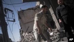 叙利亚人从阿勒颇一地区被毁的房子里抢救残余物品