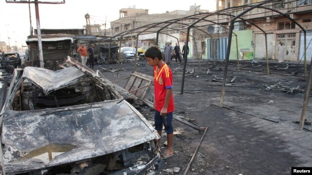 A boy looks at the remains of a burnt-out car at the site of a triple bomb attack in Baghdad's Sadr City, September 22, 2013.