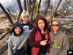 """Lisa Kermode, second from right, and her children, from left, Damien, Lola and Michael, stand outside the ruins of their home after a wildfire swept through Ventura, Calif., Dec. 5, 2017. They were home Monday night when Lisa started to smell smoke and her phone buzzed with an alert, urging residents to evacuate. """"Within an hour, it was here,"""" she said. """"We left. We grabbed nothing,"""" she said Tuesday. """"We lost everything."""""""