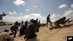 Libyan rebels duck for cover during a failed attempt to take the town of Ajdabiya from Moammar Gadhafi's forces, March 21, 2011