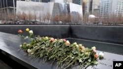 Des roses sont placées sur le monument commémoratif du 11 septembre lors de la cérémonie du 25e anniversaire pour commémorer les six victimes de l'attentat de 1993 contre le World Trade Center, à New York, le 26 février 2018.