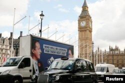 An advertising van with images of Britain's Prime Minister David Cameron and leader of the opposition Labour Party Ed Miliband drives around Parlaiment Square, central London, Britain, May 7, 2015. REUTERS/Phil Noble - RTX1BXSZ